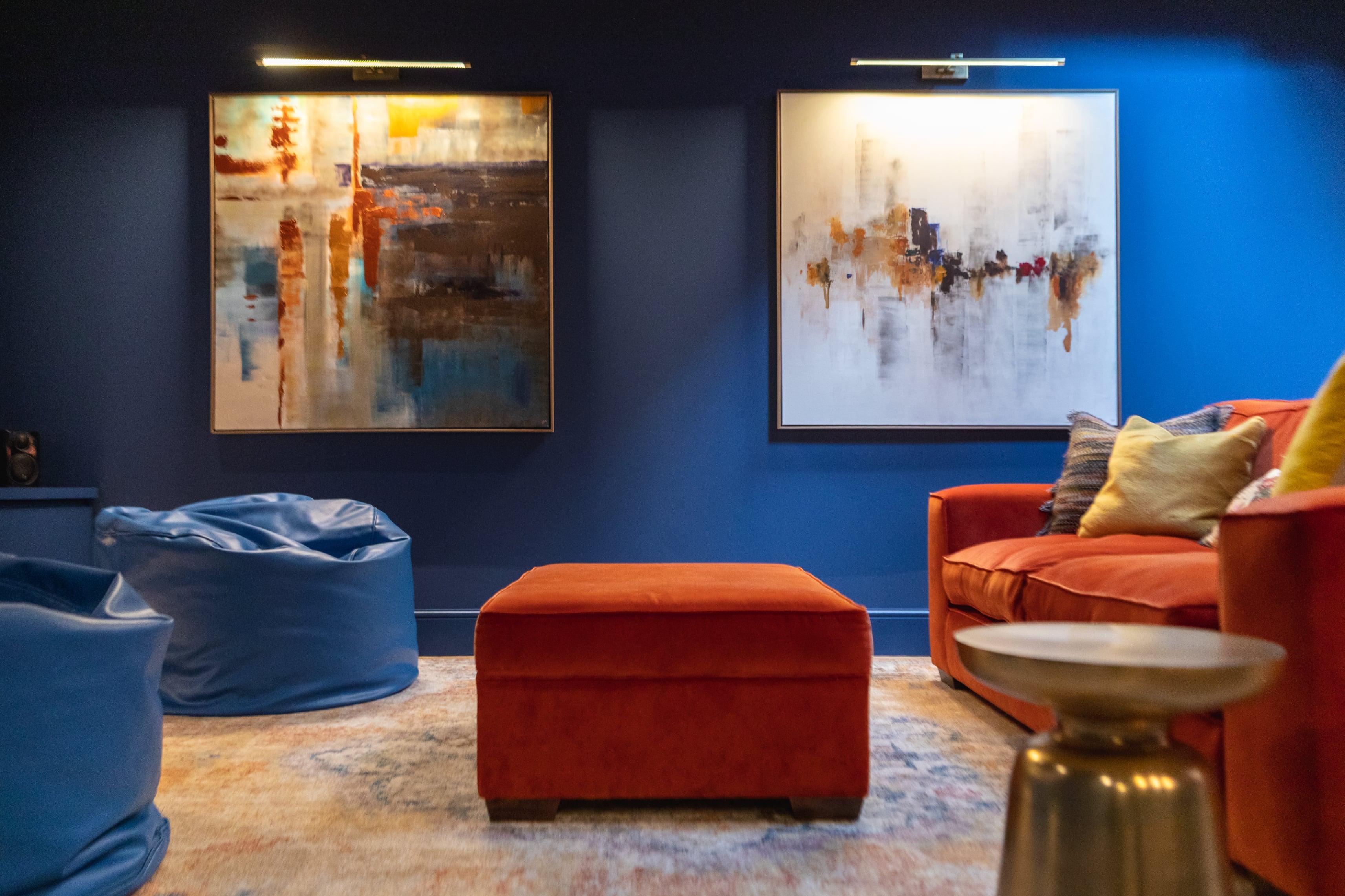 Basement interior design with blue walls and orange sofa