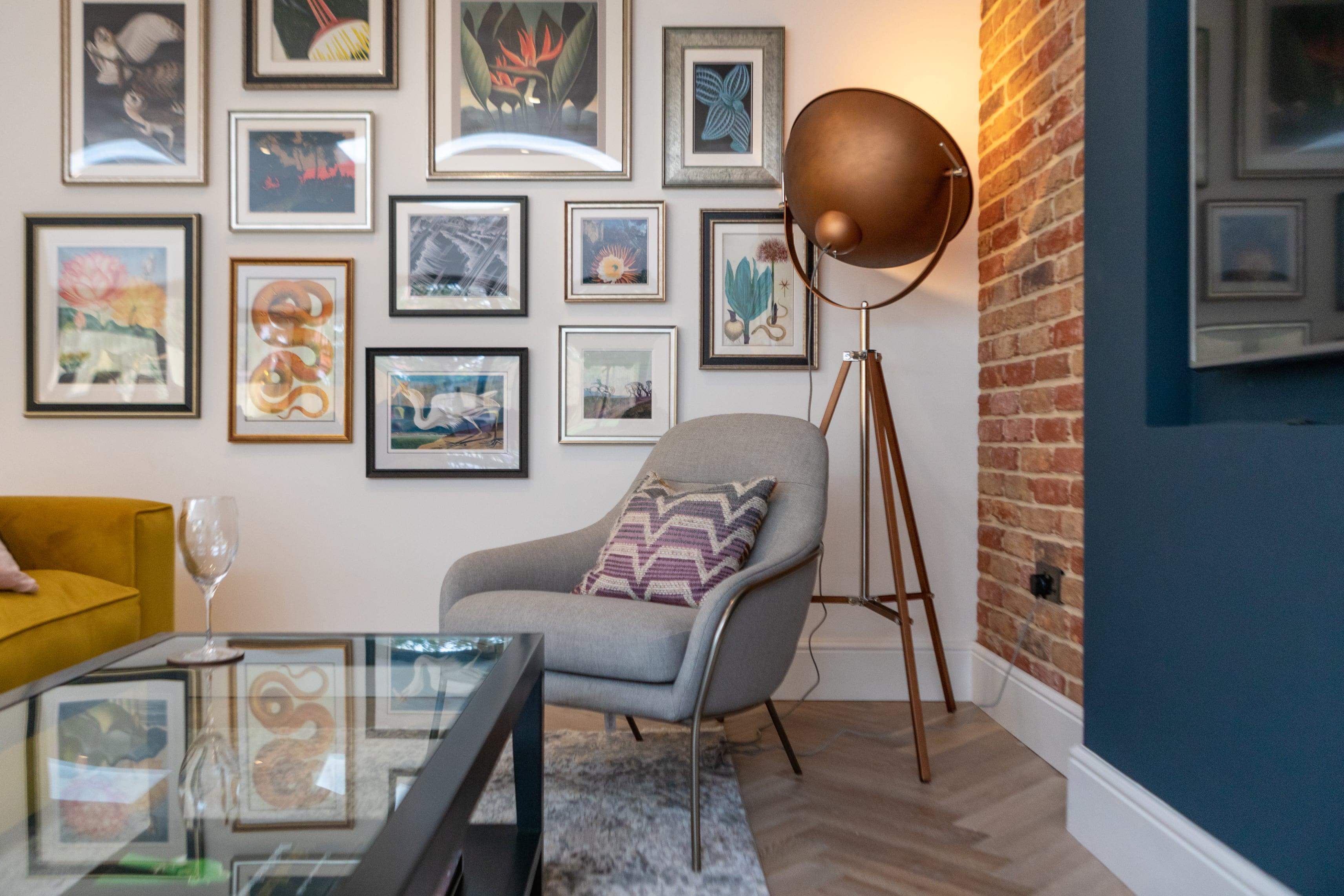 Eclectic seating area with yellow sofa and gallery wall