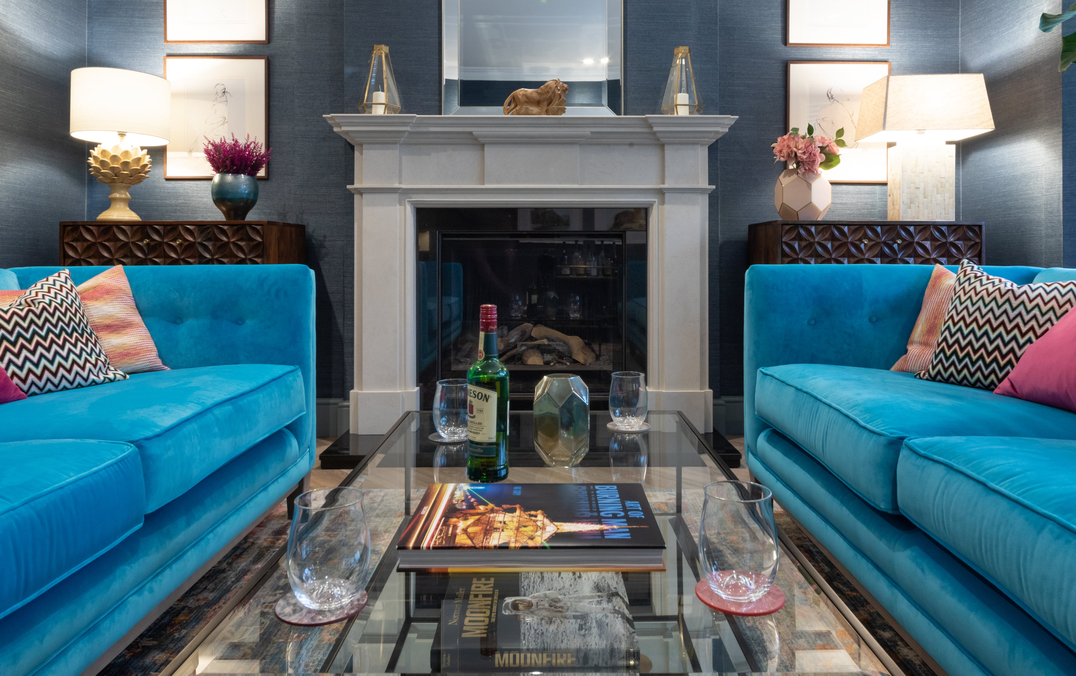 Luxury living room interior design with blue sofas and stone fireplace