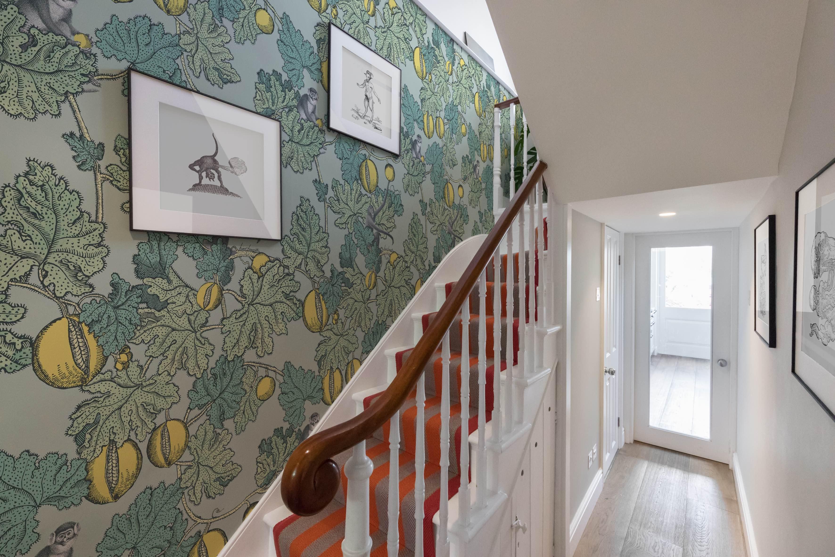 Orange stair runner with green wallpaper