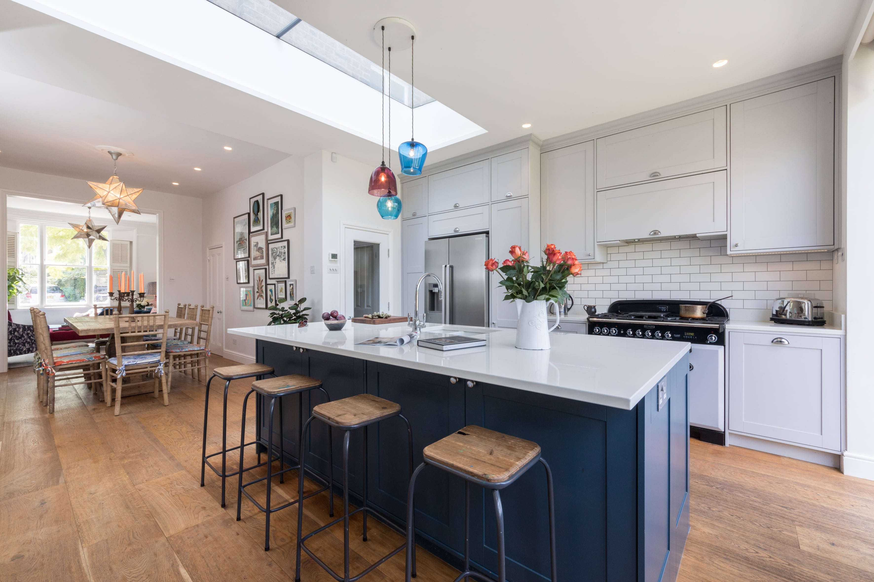 Richmond kitchen design with blue island and multi-coloured pendants