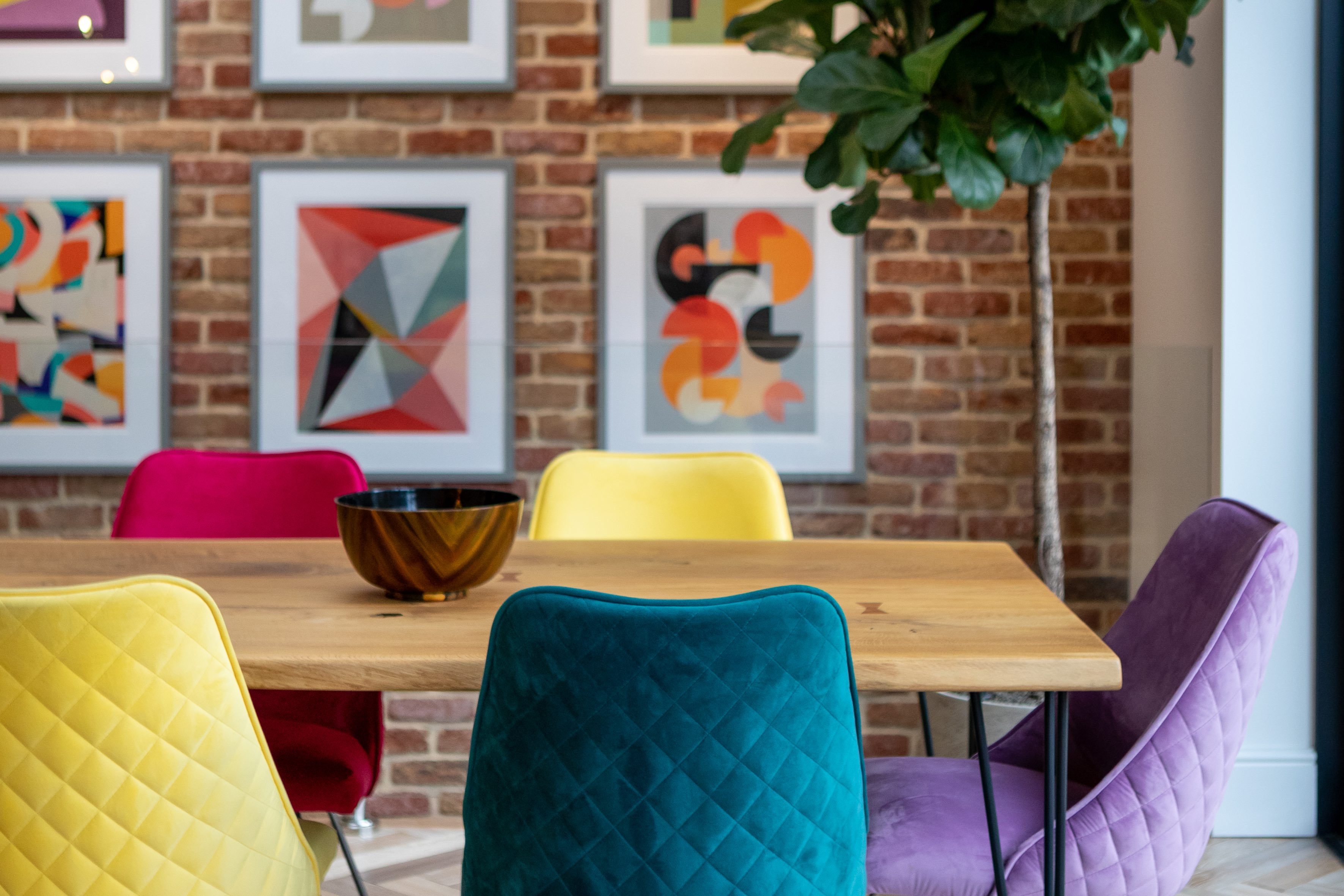 Luxury dining area with brightly coloured chairs and big plant